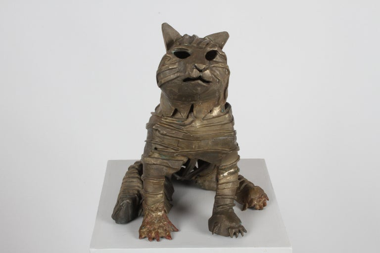 Unique cast and welded bronze brutalist sculpture of a cat in the style of a mummy. Having cast bronze gause wrapping around body with welded detail to front paw, in the style of British artist Jane Ackroyd (born 1957). Unsigned.