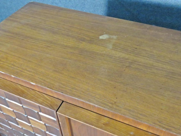 Vintage Brutalist-style dresser combining a patterned surface with rich woodgrain, accented by metal handles. This sturdy Mid-Century piece is full of crafted quality and is sure to be a lasting addition to any home. Please confirm item location