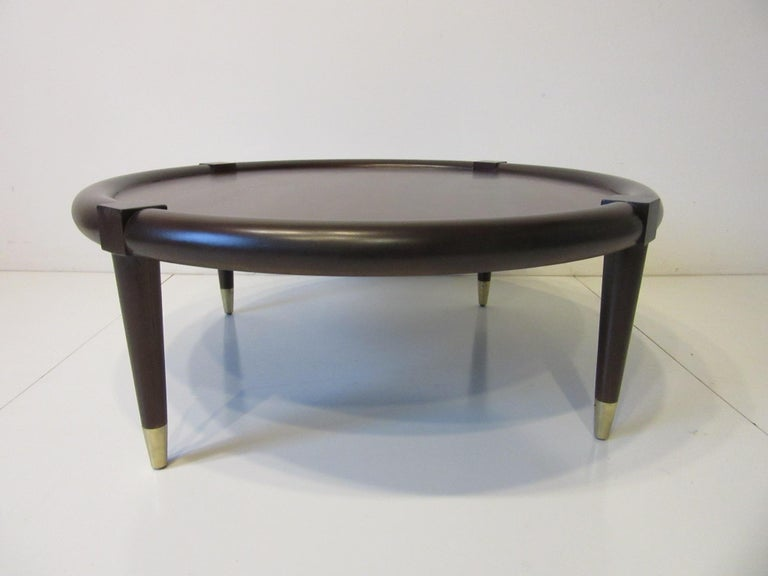 A round midcentury ebony toned bull nose coffee table with conical legs having brass tipped lower capped feet. The inserted wood center is very well grained and toned a bit lighter giving the piece some depth and can work in many different interiors