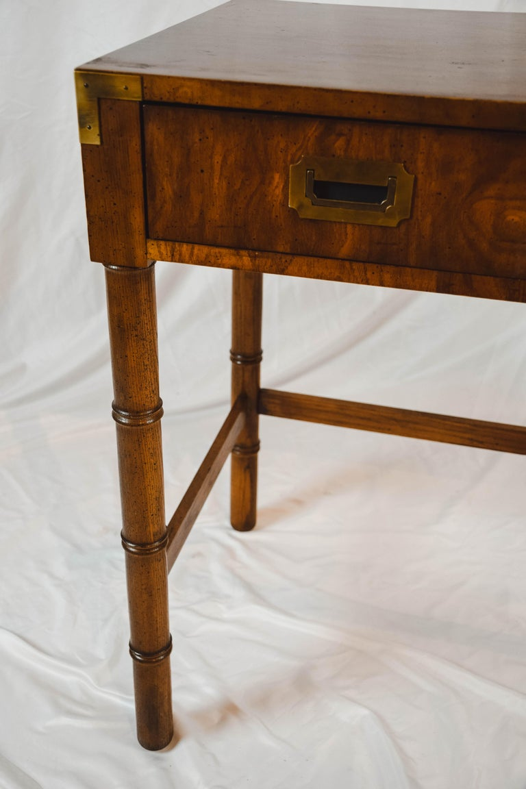 A Campaign style desk by Dixie Furniture, mid-20th century. This desk features a rectangular top resting on four legs with one drawer featuring brass hardware. Hallmarked Campaigner inside the drawer, this desk would add a touch of midcentury style