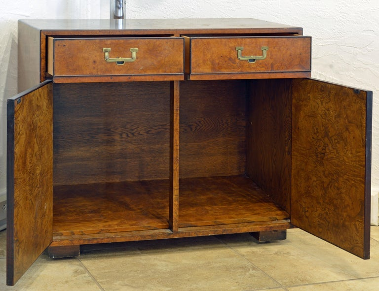 This Campaign style burled two-drawer cabinet features two drawers above two doors opening up to an interior with an adjustable shelf. It is designed and made by John Widicomb and branded in the left drawer. A special advantage is that the feet
