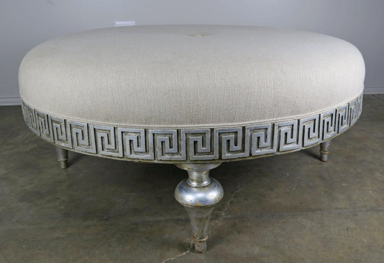 Midcentury carved silver leaf Greek key round shaped linen upholstered ottoman with self cording and center button detail. The ottoman stands on four legs.