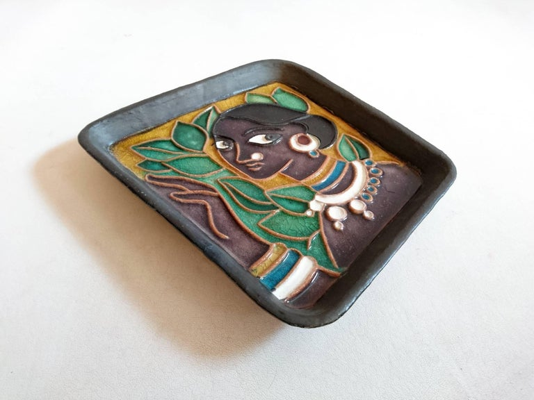 Irregular shaped charger like bowl depicting an exotic beauty. Marked on the back in the glaze TAKA-PUKA and on a sticker attached to the back: B.H.I.A, TL w/6, wall plaque, Rs 22/50.