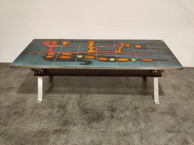 Stricking midcentury coffee table with a ceramic tiled top and a teak/chrome frame.  The table is signed by Adri.  Attractive colors and modernist design.  Untouched condition with rust marks on the side of the coffee table. Tiles are in good