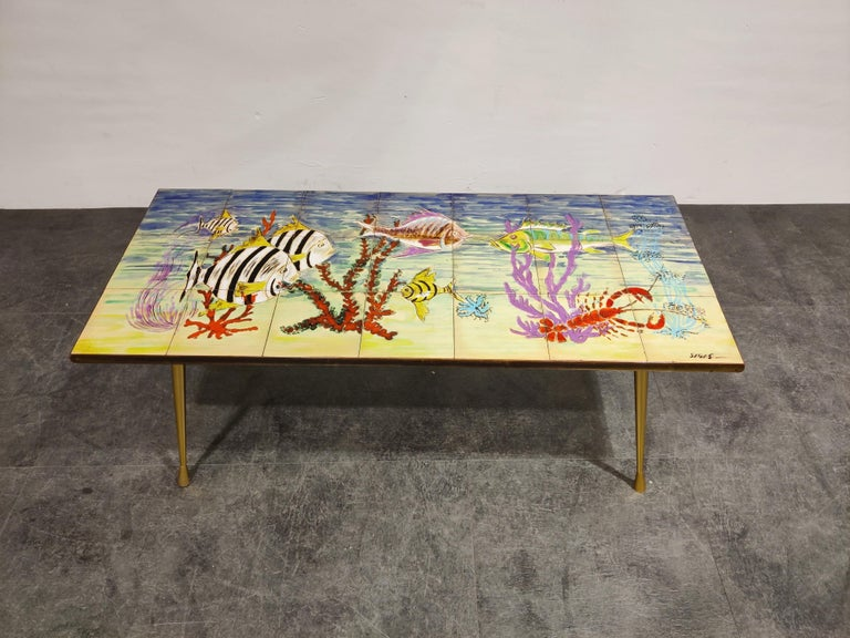 Stricking midcentury coffee table with a ceramic tiled top and elegant cast brass legs.  The table is signed by Sigis.  The coffee table depicts an underwater scene with very lively colors, a piece that really brings happiness.  Good