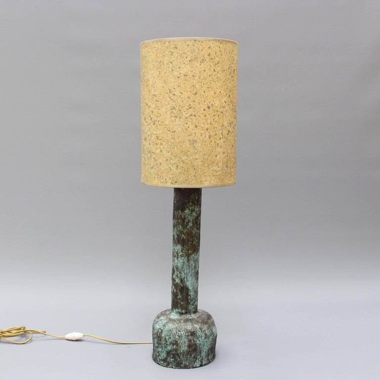 Midcentury ceramic lamp (circa 1960s), by an unknown French ceramicist. Tactile lines are etched on the surface of this imposing but elegant lamp. It has a bulbous base and a trunk like a Roman column - almost verdigris in appearance. The creator
