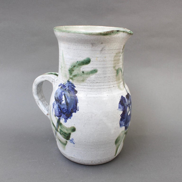 Midcentury ceramic pitcher (circa 1960s) by Albert Thiry (1932-2009). A classic Thiry design and decoration scheme, this pitcher's base color is done in a chalky-white glaze with painted blue flowers and trademark green leaves. It is elegantly