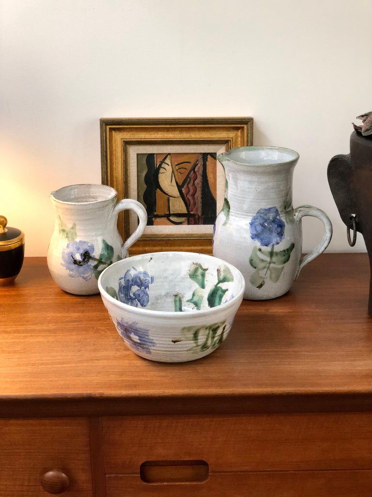 Midcentury ceramic pitcher (circa 1960s) by Albert Thiry (1932 - 2009). A classic Thiry design and decoration scheme, this pitcher's base color is done in a chalky-white glaze with painted blue flowers and trademark green leaves. It is elegantly