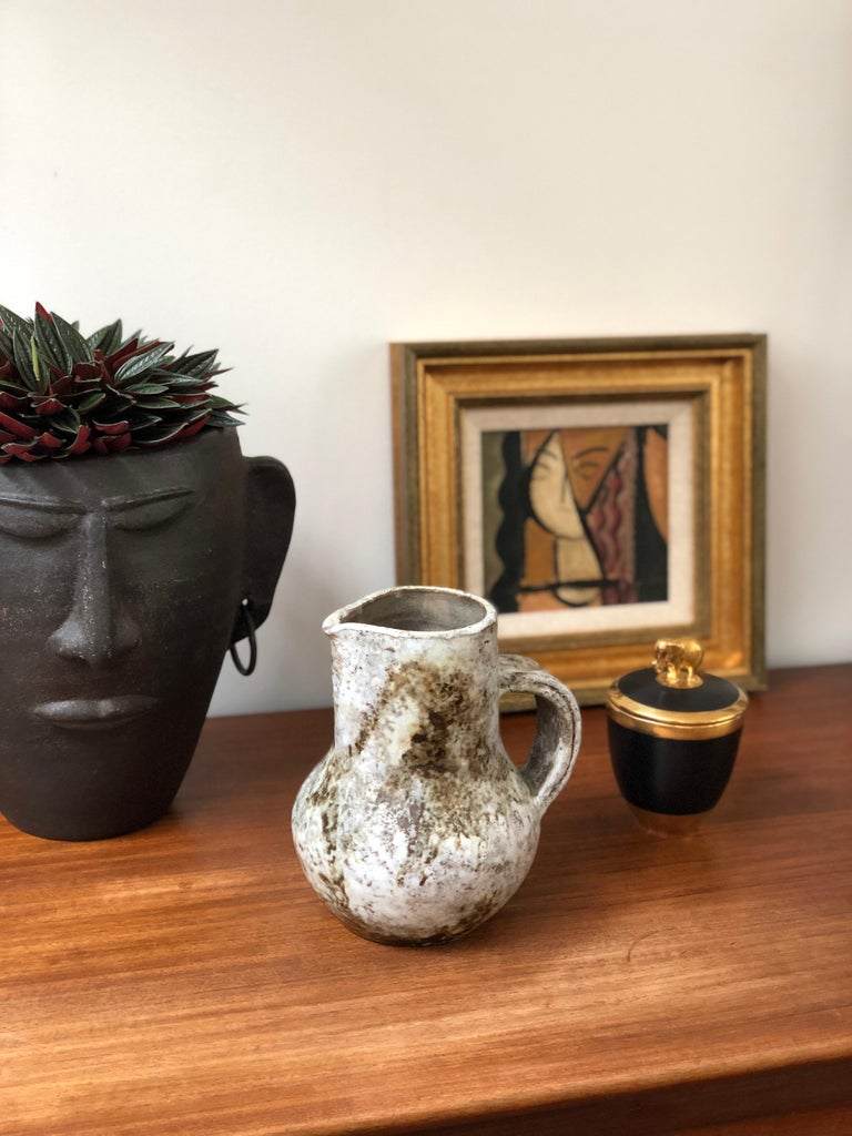 Midcentury ceramic pitcher / vase by Alexandre Kostanda (circa 1960s). This beautiful vessel presents a misty appearance with earth tones in brown and beige over a hazy, delicate white glazed base. In addition to being visually stunning, the piece