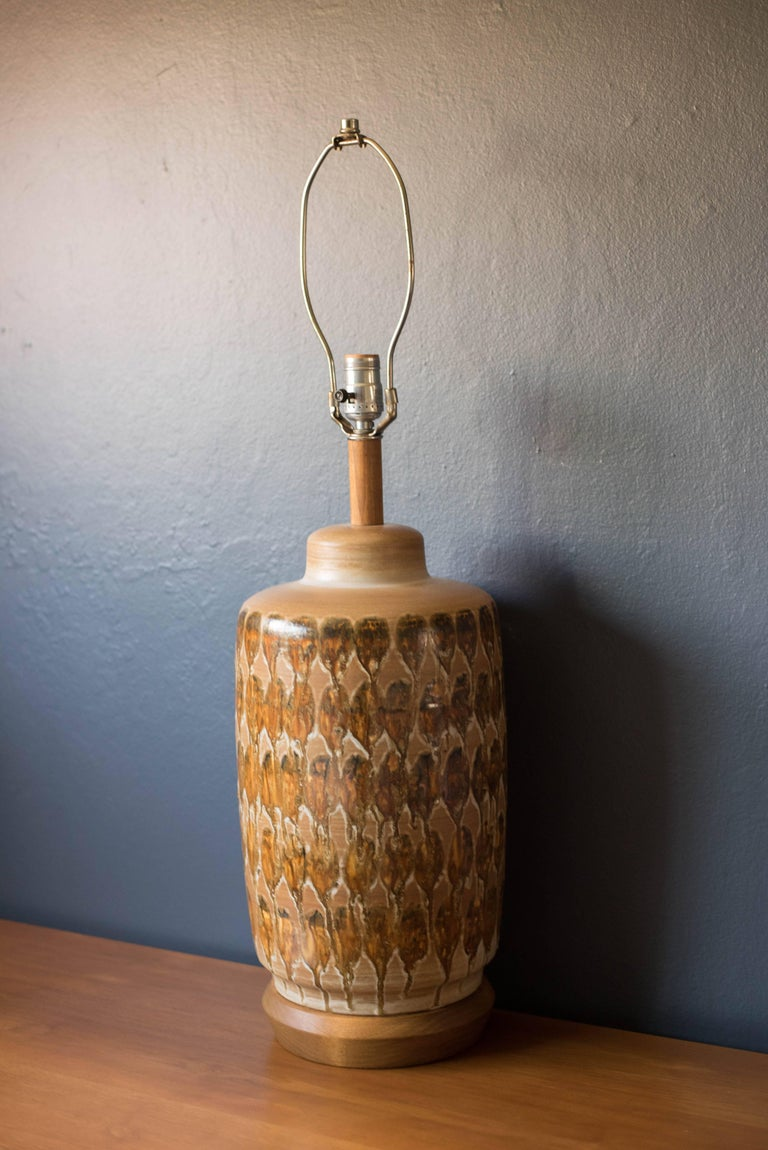 Mid-century ceramic pottery lamp, circa 1960s. This piece has a drip glazed finish in neutral tones. Features a three way switch and walnut stem and base.
