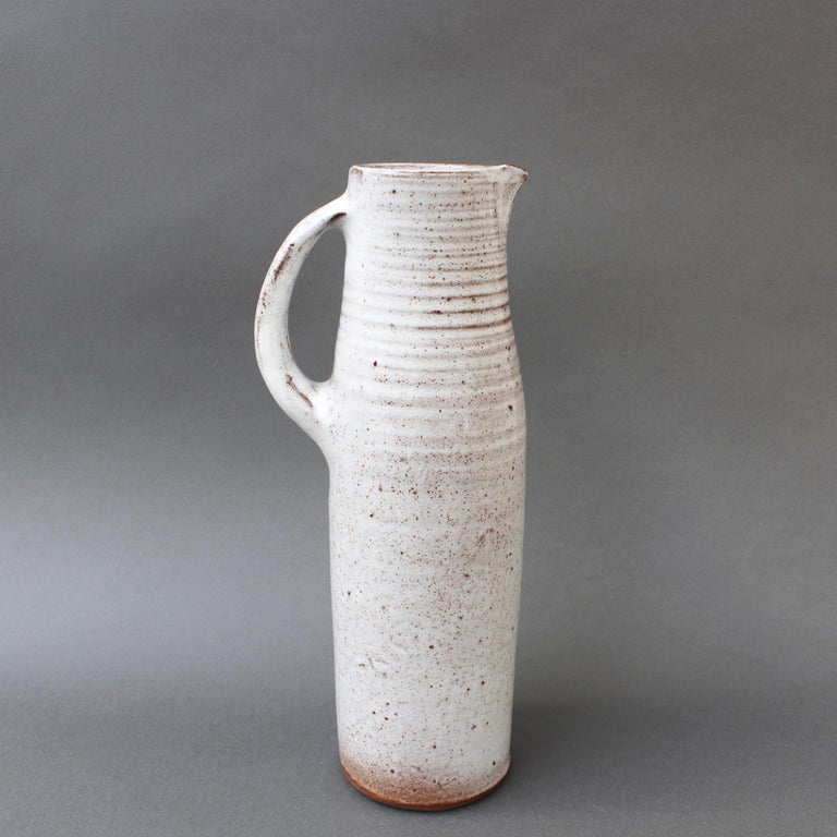 Midcentury French ceramic vase / jug by Jeanne & Norbert Pierlot (circa 1960s). With an off-white base and sandstone accents, this elongated and elegant vase with handle and spout is a delight. The glazed parts that are predominantly white are
