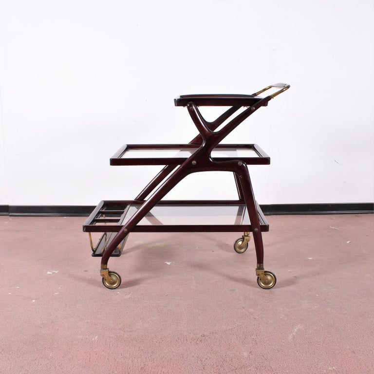 Geometric shapes in curved wood in this beautiful bar trolley attributed to Cesare Lacca. Three glass shelves with a small removable tray at the top, brass wheels. Sturdy structure without damage.