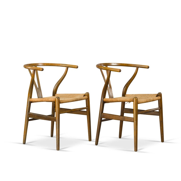 These two CH24 wishbone armchairs are designed by Hans J. Wegner. And produced in the 1950s by Carl Hansen & Søn in Denmark. The frame is made from oak. These chairs were painted originally and time has worn off the paint in a nice patina. The