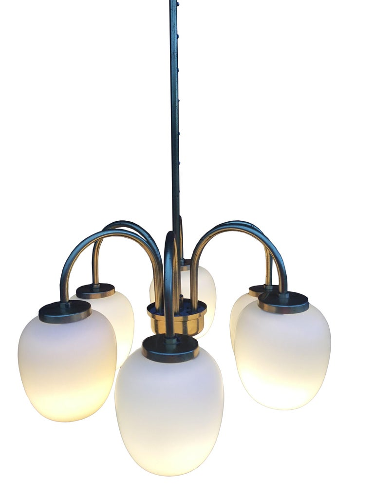 The most beautiful chandelier in an elegant combination of patinated brass and opal glass. Provides a stunningly beautiful and soft light – here fitted with 25W bulbs. All opal glass are intact.  The chandelier measures approximately Ø45cm and each