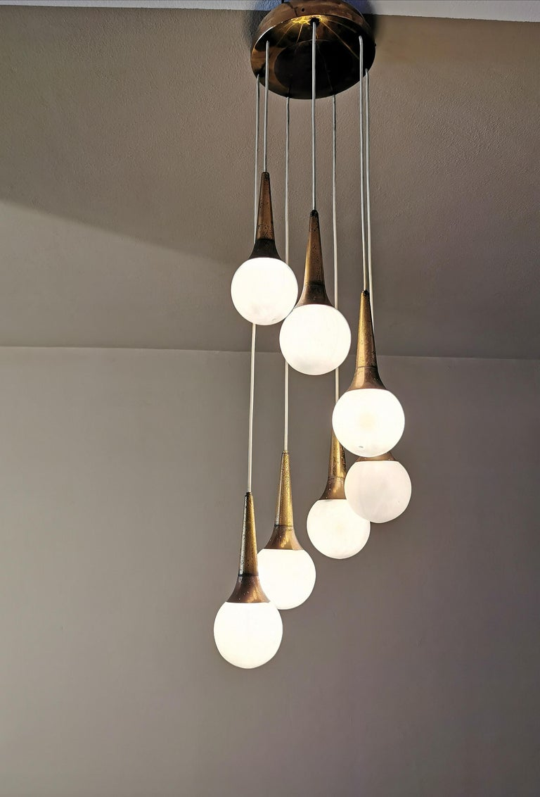 Rare and elegant cascade chandelier designed in the 1950s by the famous Italian design company Stilnovo. The chandelier has of conical brass pendants with 7 spherical bowls in satin opal glass.