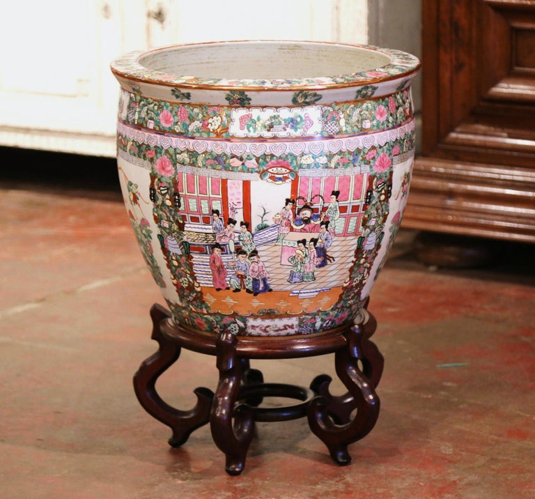 This elegant and colorful vintage fishbowl standing on a carved fruitwood base was created in China, circa 1960. Round in shape, the large, exotic porcelain planter features Classic oriental scenes with Chinese people throughout, and embellished