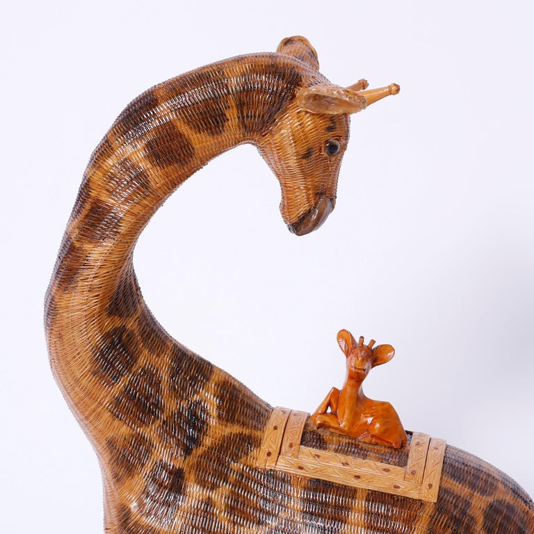 From the famed Shanghai collection a giraffe expertly crafted with tightly woven wicker. The removable lid is a carved wood baby giraffe along for the ride.