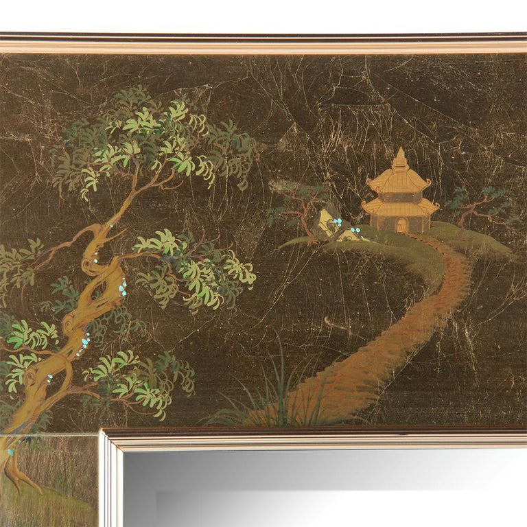 American-made, hand painted, chinoiserie style mirror by Labarge of Holland Michigan. The original bevelled mirror is set within a matte brushed gold colored glass frame which is hand painted in an Asian or 'chinoiserie' style featuring flowers,