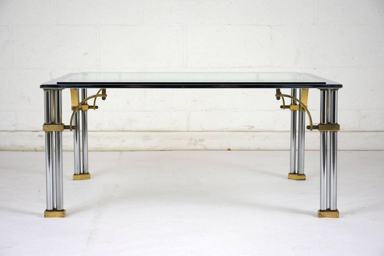 This 1960s Mid-Century Modern Square Coffee Table features an Art Deco-inspired base with chrome legs and glass support and brass accents. The tabletop is made of 3/8