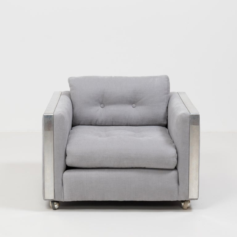 Designed in the style of Milo Baughman, this sleek Midcentury armchair has been newly upholstered in a sumptuously soft and airy grey Linara fabric that compliments the chrome detailing perfectly.   With its clean lines and cool aesthetic it
