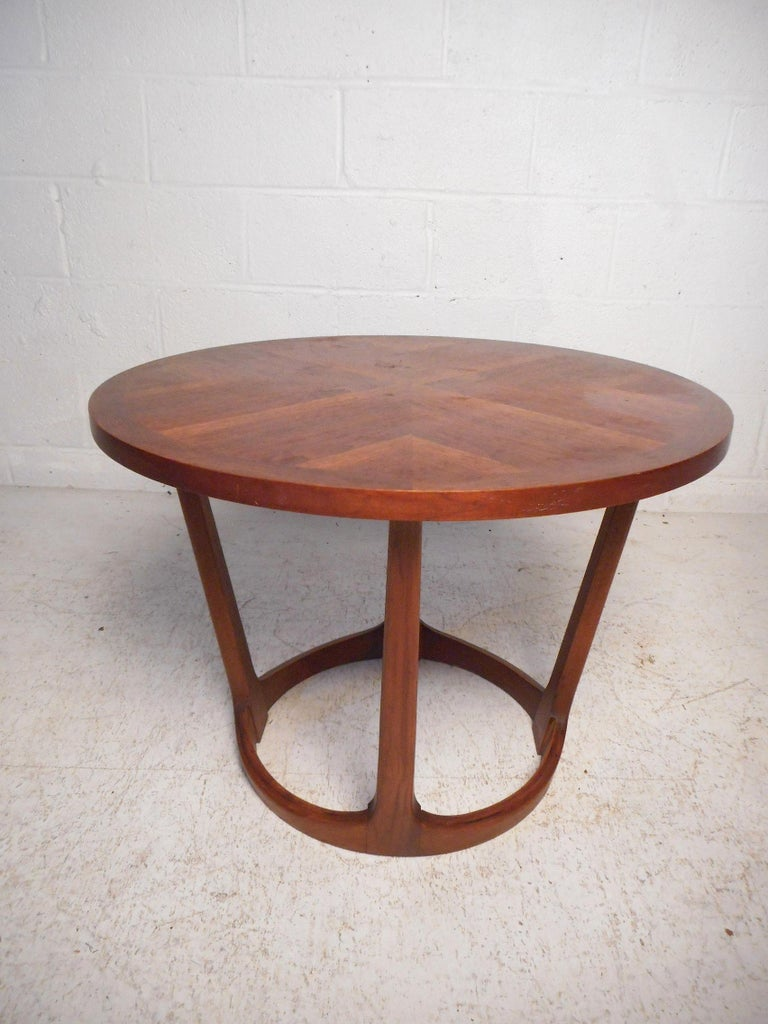 This stylish midcentury side table features a sturdy walnut construction, tapered supports, and a circular tabletop showcasing an interesting grain pattern. Made by Lane in 1964, this table is sure to make a great addition to any modern interior.