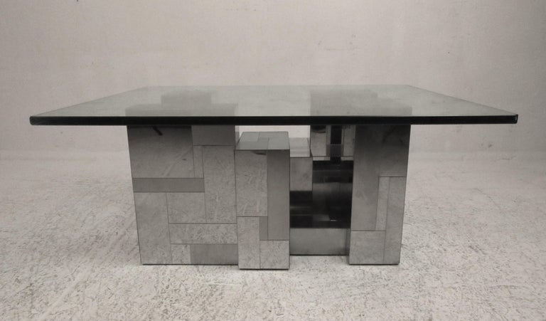 A stunning vintage modern coffee table by Paul Evans for Directional. This sleek table features a chrome patchwork base with a 3/4 inch thick rectangular glass top. The Brutalist style design is sure to make an impression in any setting. Please