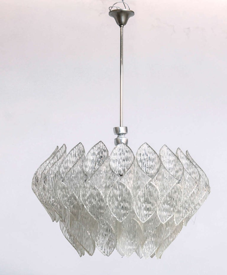 Midcentury Kalmar style chandelier containing a chrome frame with shades made of folded Lucite and in the middle one round iced glass. Chromed hardware.  Measures: height 35 cm with stem 80 cm, width 60 cm.