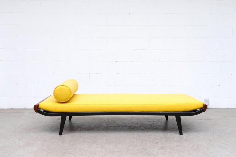 Beautiful 1960's Cleopatra style day bed by A.R. Cordemeyer. Lightly refinished teak wood ends with dark grey metal enameled frame and 'Auping' tag on mesh springs with new bright sunshine yellow mattress and matching bolster. Frame in original