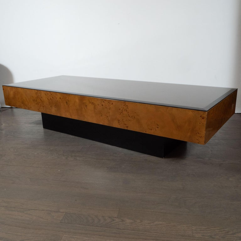 This elegant Mid-Century Modern cocktail table attributed to the esteemed Mid-Century Modern designer Milo Baughman, circa 1970. It features a volumetric rectangular top in bookmatched and burled Carpathian elm with an ebonized walnut base in the