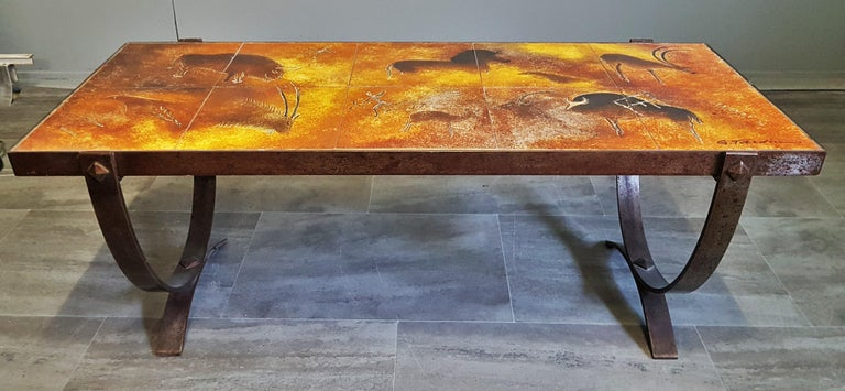 Midcentury coffee table by Georges Tardieu, Vallauris, France, 1960s.  Tiles with stone age decoration. Solid cast iron base.  Strong colors.