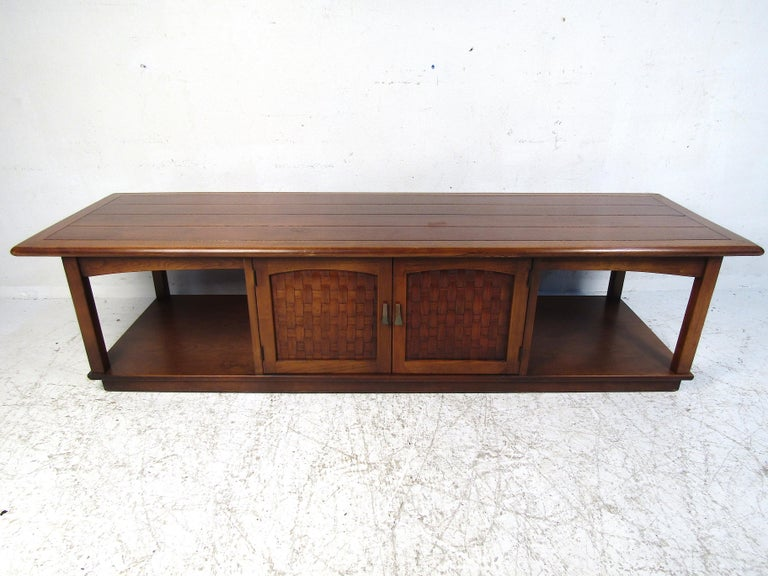 Nice midcentury coffee table by Lane Furniture Co. Interesting design with two tiers, rounded edges, and a storage compartment. Woven accents on the cabinet door-fronts.