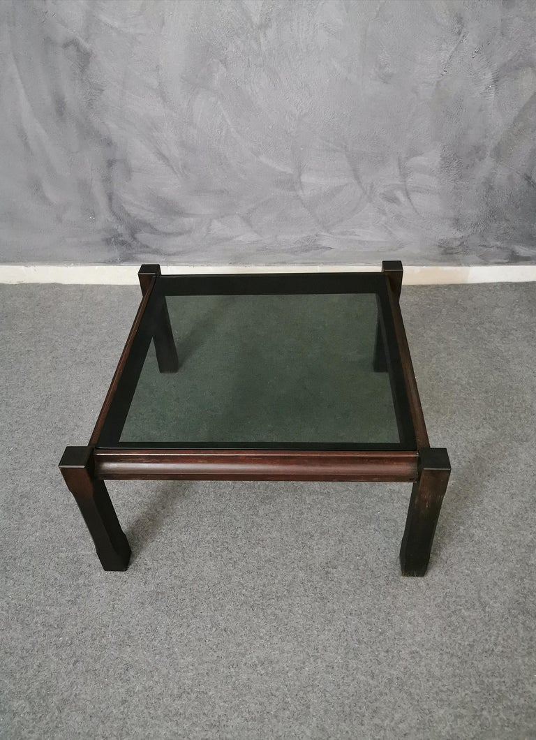 Square rosewood coffee table with removable smoked glass top. The coffee table has 4 wooden feet that protrude slightly in the part of the glass top, Italian production of the 1960s.