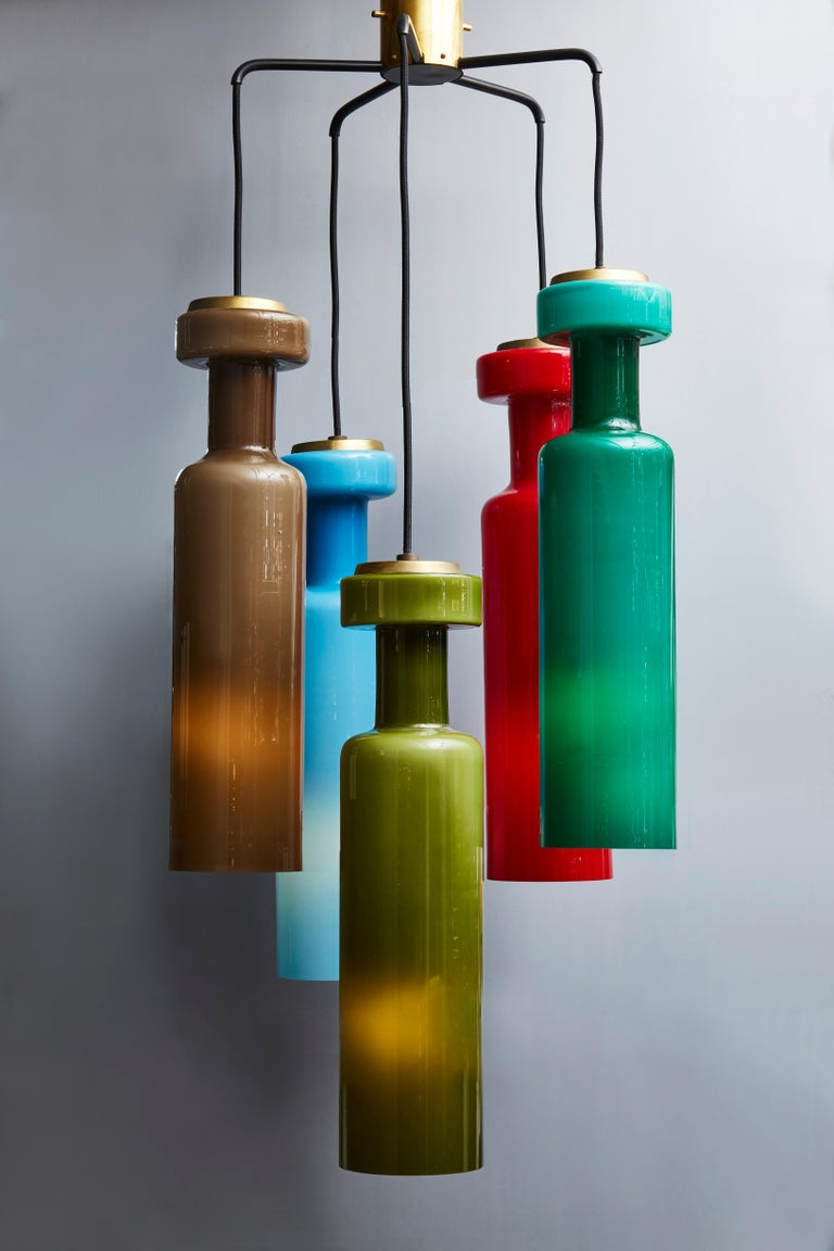 Midcentury chandelier made of five colored glass pendants suspended by their adjustable wire to a star-shaped metal structure.