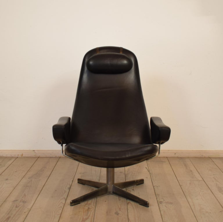 This elegant Contourette Roto armchair by Alf Svensson was designed in the 1960s in Denmark and was produced by DUX. The chair is covered in black leather and has a single head rest. The frame is made out of metal and has got a turning foot with