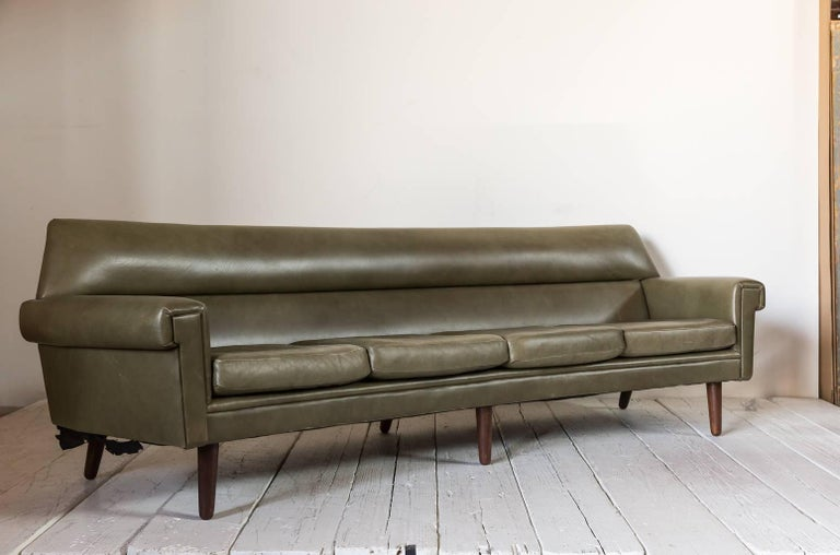 Midcentury Olive Green Leather Sofa With A Slightly Curved Back Tapered Cylindrical Leg And