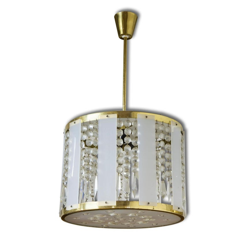 Czechoslovak crystal chandeliers, made in the 1970s. An excellent quality piece, it features a cut glass beads and pendants hanging from the brass centre and slices of plexiglass around the chandelier. In very good vintage condition, consistent with