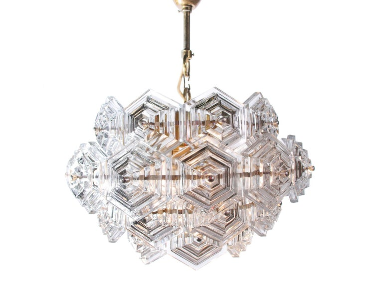 Dandelion chandelier with hexagonal glass prisms on a brass frame made by VEB Kristall Leuchten in the GDR in the 1960s. The lamp takes three large Edison bulbs. Measurements: diameter 16.5 in. / 42 cm, height 10.2 in. / 26 cm, ceiling height: