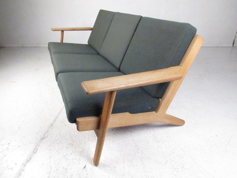 This beautiful vintage modern three seat sofa boasts a solid blonde oak frame with wide sculpted arm rests and splayed legs. A comfortable sofa with six removable cushions covered in a plush green fabric. This well made Danish piece was designed by