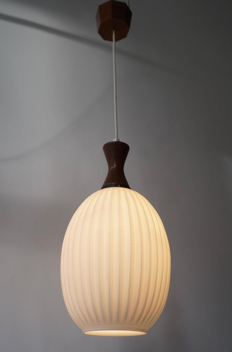 Midcentury Danish glass and wood ceiling light. Measures: Diameter 22 cm. Height fixture 25 cm. Total height 53 cm.