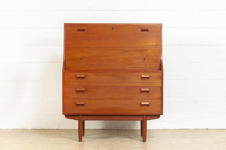 This midcentury Danish modern teak secretary desk designed by Børge Mogensen for Søborg Møbelfabrik is circa 1950. The Classic Scandinavian Modern design has clean Minimalist lines and gentle curves and is well-crafted from teak wood with beautiful