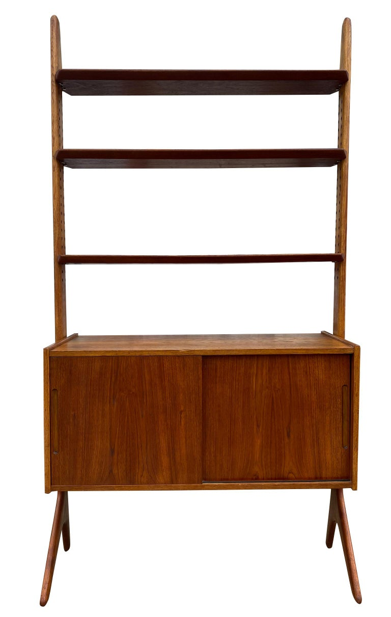 Unique midcentury Danish modern freestanding teak wall shelf unit Jutex Designed by Hovmand Olsen. Has 2 solid oak and teak uprights with 3 adjustable solid teak shelves and has a lower teak cabinet with sliding doors, (1) adjustable shelf (2)