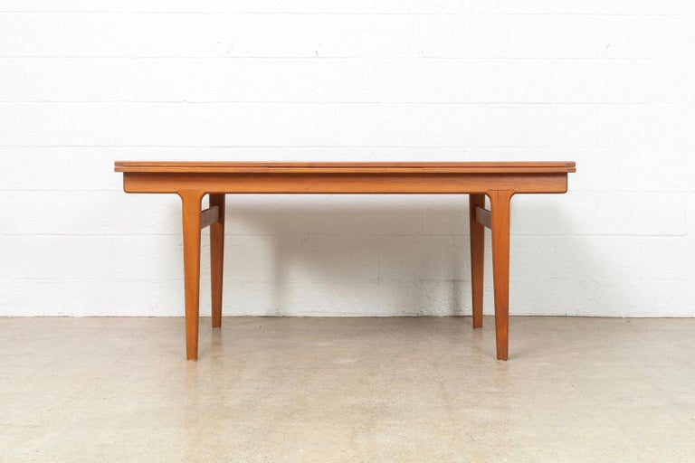 This vintage Mid-Century Modern Henning Kjaernulf for Vejle Moebelfabrik expandable dining table made in Denmark circa 1960 has an elegant Minimalist aesthetic and a clean, unimposing Danish modern design. It is exceptionally crafted from solid teak