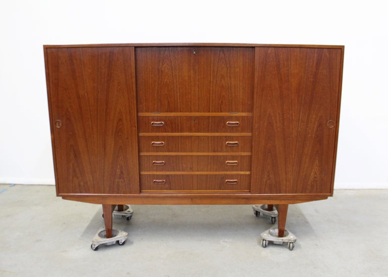 Offered is a teak credenza/highboard by Omann Jun. Features sliding doors with shelving, 4 drawers, and a pull-down surface. Comes with a key to lock drawers and secretary. It is in great condition, showing some age wear, (surface scratches/chips,