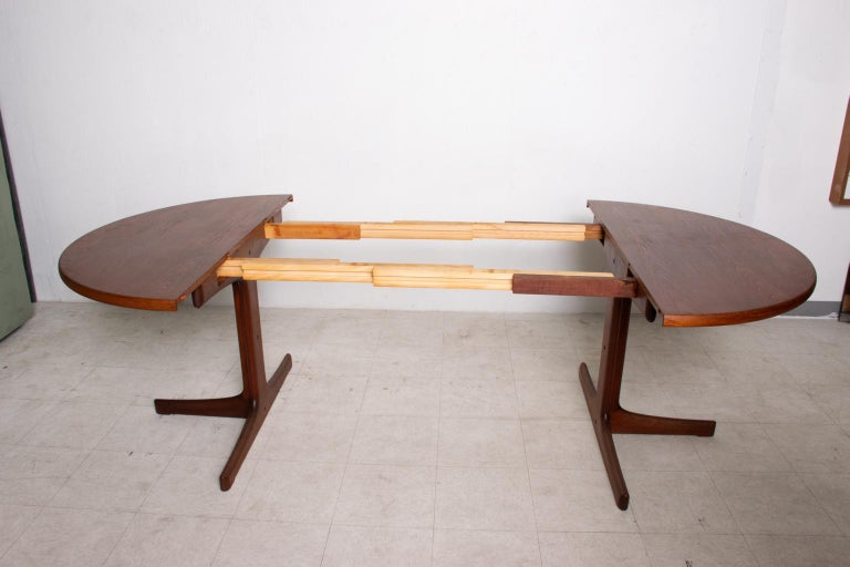 For your consideration, a round dining table can be extended into an oval dining table. It will allow us to seat up to 10 persons. Made in Denmark, circa the 1980s. Teak wood. No markings from the maker.   Dimensions: 95