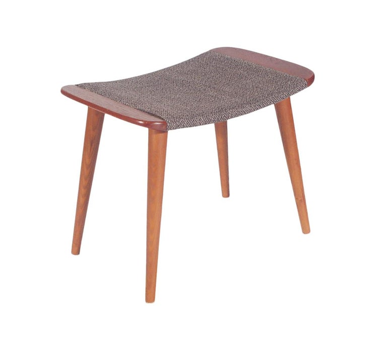 A Classic clean line designed ottoman or foot stool from Scandinavia, circa 1960s. It features teak wood with original tweed upholstery.
