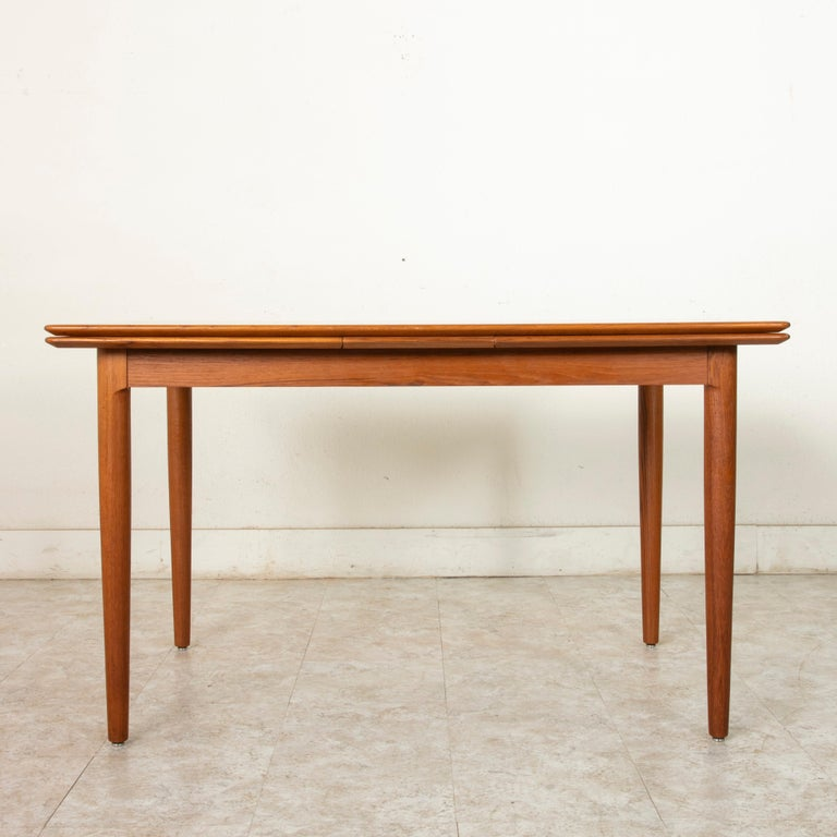 This Mid-Century Modern Danish dining table constructed of teak wood features a nearly 50 inch long by 34 inch wide top that rests on sleek tapered legs. Draw leaves add an additional 19.5 inches to each end allowing for a total length of 88.5