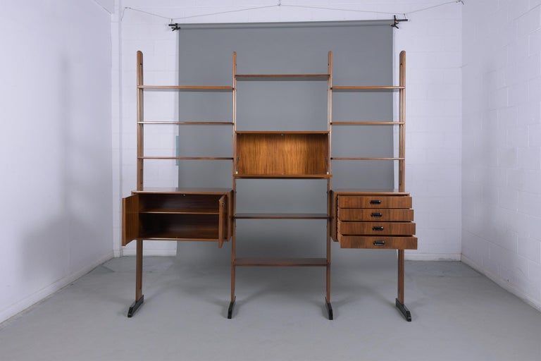 An extraordinary Mid-Century Danish modern bookcase hand-crafted out of walnut, fully restored and newly refinished in a dark walnut color with an ebonized finish and a lacquer finish. This beautiful bookcase features three cabinets, one of them