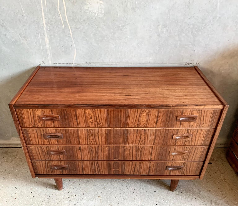 Chest of drawers in rosewood featuring four drawers and tapperes legs.
