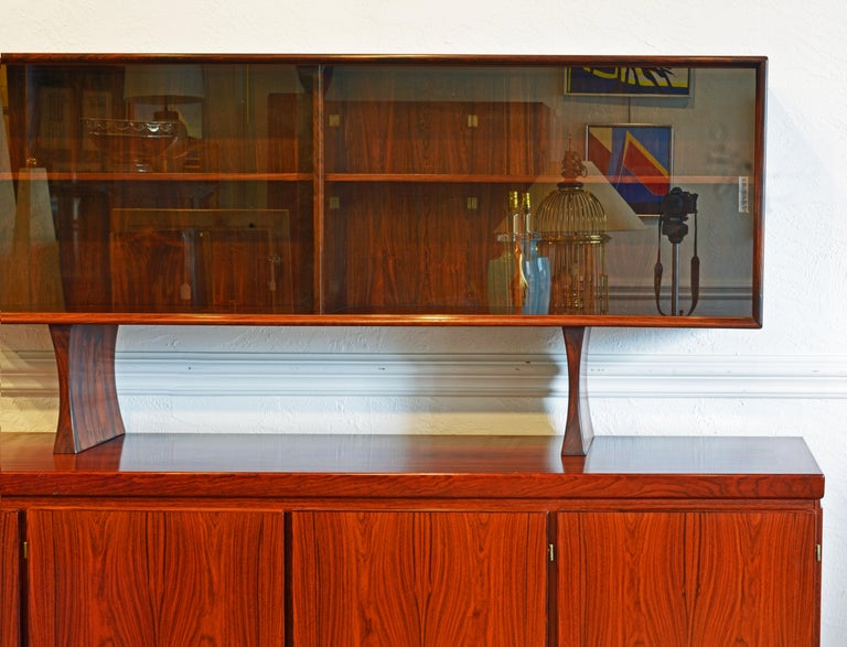 A superior design rosewood four-door sideboard/credenza with a hutch display cabinet by Danish manufacturer, Skovby Mobler dating to circa 1970. Each door is veneered with book-matched rosewood, The credenza rests on a recessed plinth base. One door