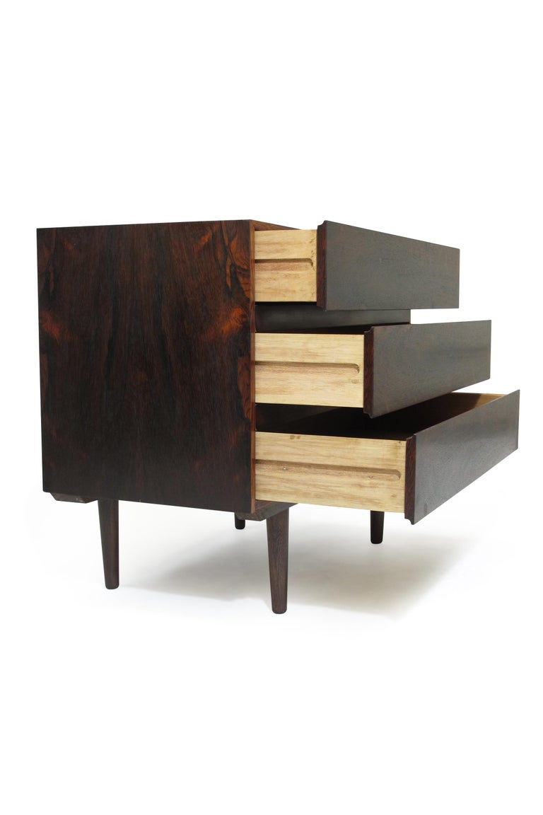 Three-drawer dresser crafted from rich, dark rosewood with bookmatched grain and set on tapered legs. Finely restored.